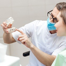 Dentist showing patient dentla implant model