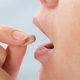 Woman taking oral sedative pill