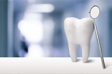 Image of a tooth with a dental mirror leaning against it and a dental office blurred in the background